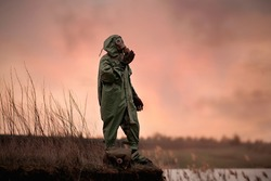 A man in a gas mask and protective suit stands on the edge of the abyss. the only survivor of an environmental disaster. Radiation pollution, toxic environment. The concept of loneliness.
