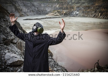 A man in a gas mask with hands raised