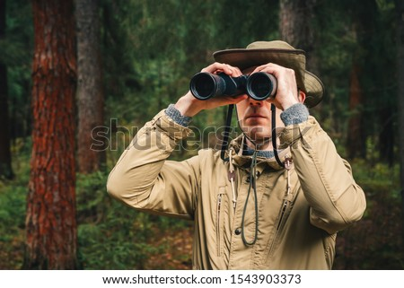 A man in a hat and uniform green and beige holds binoculars and looks into the distance, Ranger watching the territory, the protection of the reserve Stock photo ©