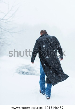 a man in a leather coat covered in snow - Shutterstock ID 1016146459
