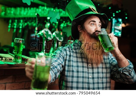 A man in a leprechaun hat and with a beard drinks beer in a bar. He celebrates St. Patrick's Day.
