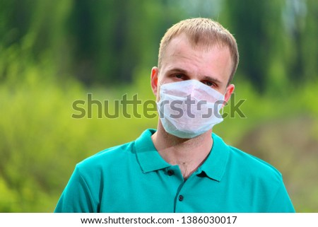 A man in a mask on a blurred background of nature #1386030017