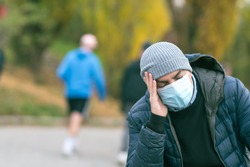 A man in a medical mask in the park with his hand on his head due to a headache. Protection against coronavirus COVID-19 SARS-CoV-2 infection. Selective focus