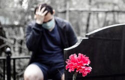 A man in a medical mask mourns, holding on to his head, sitting at the tombstone. Death from a coronavirus. A relative of the deceased person in the cemetery. A medical mask weighs on a tombstone.