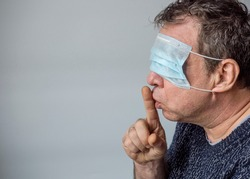 A man in a medical mask put a finger to his lips. Coronavirus conspiracy thesis concept