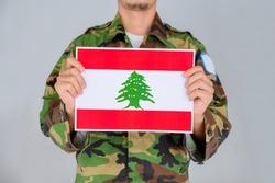 A man in a Military shirt holding the flag of Lebanon. Pray for Lebanon. Pray for Beirut.