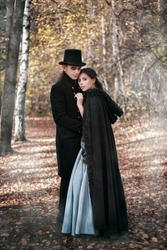 A man in a nineteenth century suit and a woman in a historical dress. Young man and woman in historical costumes in a gloomy forest