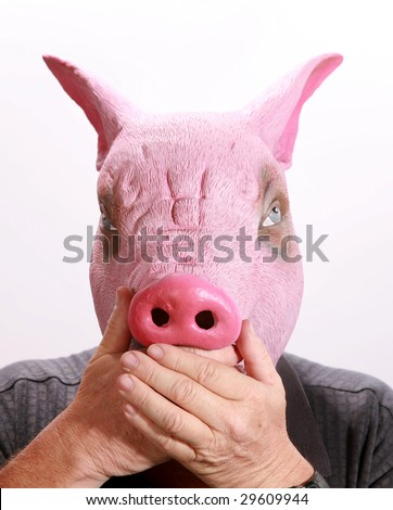 "A man in a Pig Head puts his hand over its mouth in the classic proverb ""speak no evil"""