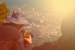 A man in a protective hat from the sun. A professional photographer shoots a landscape from a cliff. In the distance the sea, rocks and the coastal city. Tinted. Copy space.
