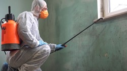 A man in a protective suit, glasses and a respirator sprays a disinfectant. Mold remediation specialist in uniform inspects walls and spraying pesticide on damaged wall with sprayer