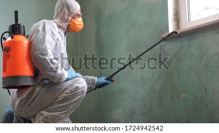 A man in a protective suit, glasses and a respirator sprays a disinfectant. Mold remediation specialist in uniform inspects walls and spraying pesticide on damaged wall with sprayer Stockfoto ©