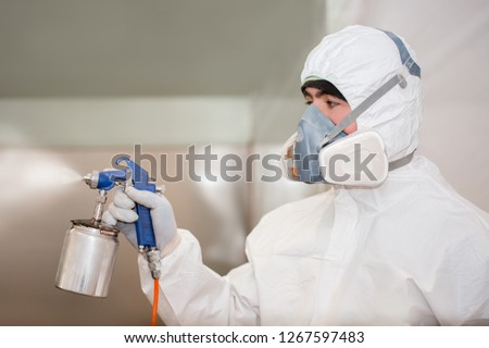 A man in a protective suit in the laboratory conducts disinfection. Specialist clothing protecting from chemical poisoning in the industry and treatment with insecticides. #1267597483