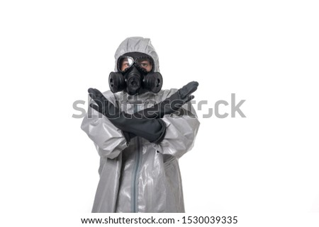 A man  in a protective suit with a protective gas mask, posing while standing on a white background. Indicates stop sign with his hands. Isolated