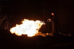 a man in a raincoat with a hood holds a flamethrower that gives a lot of flame, a rehearsal for a performance for a fireshow with a bright fire, the danger of fire for an artist taming the fire