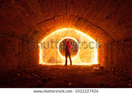 Stock Photo A man in a red hood opened a portal, a circle of sparks, an Underground city, adventures in a lost world, steel wool photo