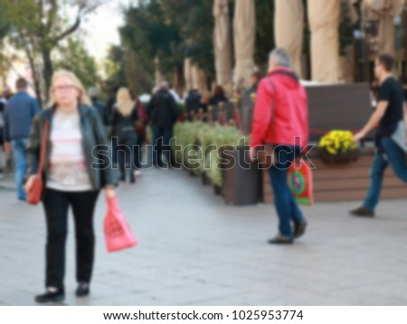 A man in a red jacket is back from shopping,blur #1025953774