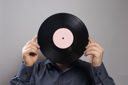 A man in a shirt holds an old vintage vinyl record instead of his head. The idea of a love of antiques.