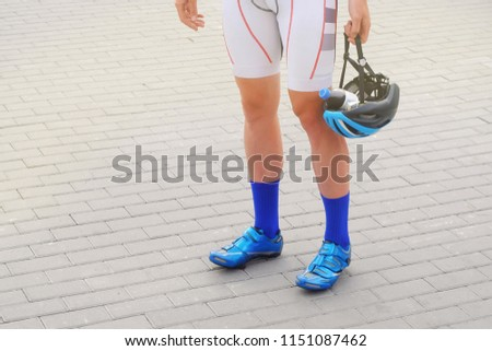 a man in a sporty suit in blue socks and shoes holds a helmet in his hand in which a bottle of water, a theme of sport and recreation  #1151087462