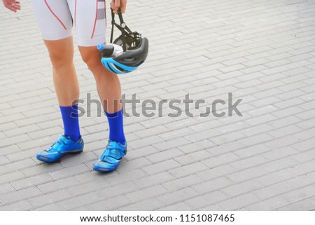 a man in a sporty suit in blue socks and shoes holds a helmet in his hand in which a bottle of water, a theme of sport and recreation  #1151087465