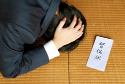 A man in a suit and a reminder. Japanese documents sent for late payments of debts, taxes and subscriptions. Translation: reminder letter.