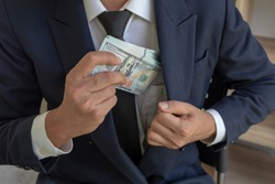 a man in a suit placing money in his jacket pocket