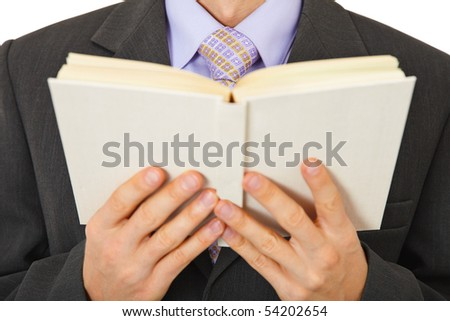 A man in a suit reads a book