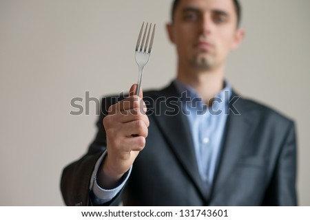 A man in a suit with a fork in his hand