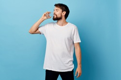 A man in a t-shirt and trousers on a blue background drinking water from a glass