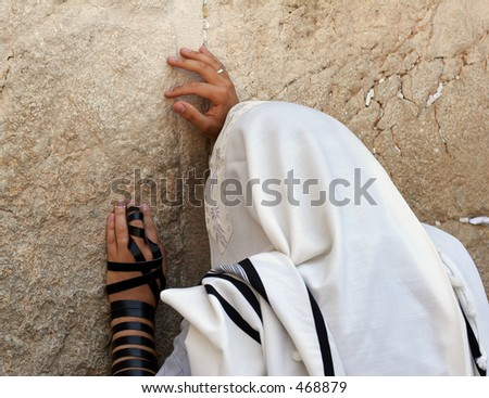 a man in a talit praying at the wailing wall.