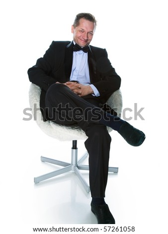 A man in a tuxedo bow tie sitting in a white chair on a black background