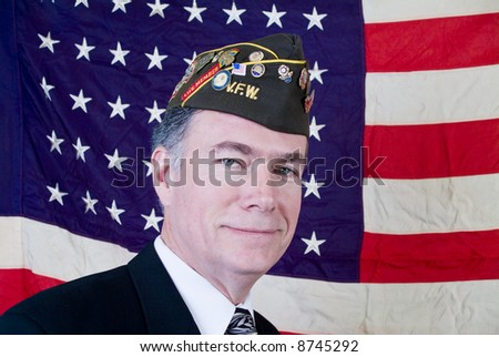 A man in a veteran of foreign wars cap standing in front of a forty-eight star US flag.