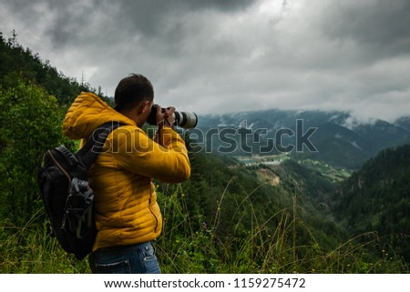 A man in a vibrant yellow coat and with a backpack is taking picture of the misty mountains and valley on a rainy cloudy day