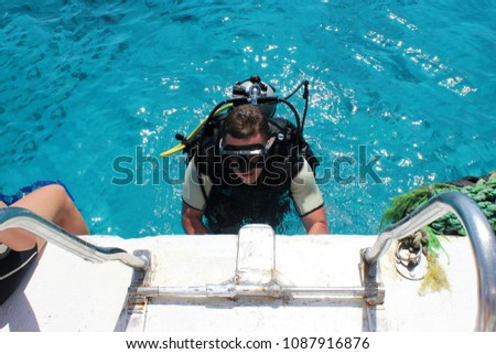 a man in a wet suit, with an aqualung, mask and a balloon. A diver in diving gear is preparing to dive #1087916876