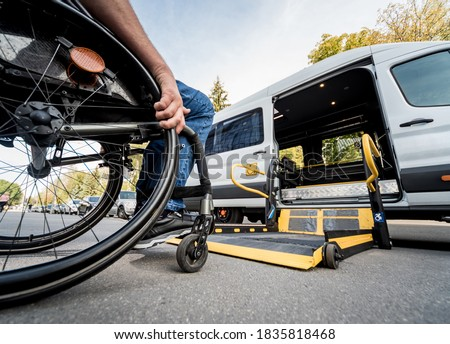 A man in a wheelchair moves to the lift of a specialized vehicle  ストックフォト ©