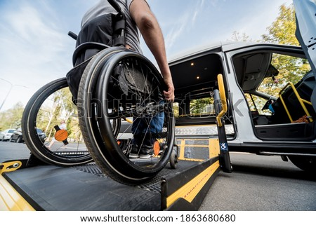 A man in a wheelchair moves to the lift of a specialized vehicle  Photo stock ©