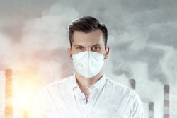 A man in a white mask because of air pollution in the city on the background of pipes. Protecting the body from global warming. Dust mask in the city. The concept of air pollution, carbon dioxide.