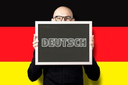 A man in a white shirt and jacket holding a sign with the text deutsch on the background of the flag of Germany. German learning concept, business deutsch.