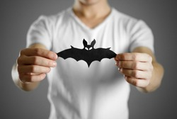 A man in a white t-shirt holds a black silhouette of a bat. Close up.