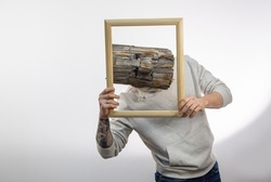 A man in a wooden mask with a tattoo on his arm holds a wooden baguette for a painting and looks out of it on a light background.