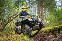 A man in a yellow helmet rides a Quad bike through the woods. Quad bike on a forest road. Journey through the forest on a Quad bike. Sale and rental of ATVs. Driving on bad roads.