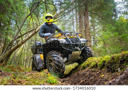 A man in a yellow helmet rides a Quad bike through the woods. Quad bike on a forest road. Journey through the forest on a Quad bike. Sale and rental of ATVs. Driving on bad roads. Stock photo ©