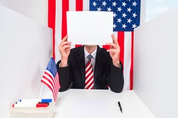 A man in an American flag tie covered his face with a blank sheet of paper. Person and flags of the USA. A man in a business suit against the background of American flags. American patriotism.