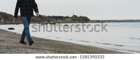 A man in an autumn short coat and blue jeans walks along the seashore on a cloudy autumn day. Banner for the site header.
