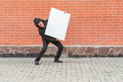 A man in black clothes stands against a red brick wall and holds a blank white canvas in front of him to paint