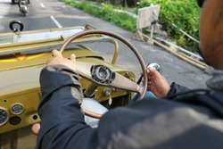 A man in black drive an old military vehicle with view of dashboard and steering wheel.