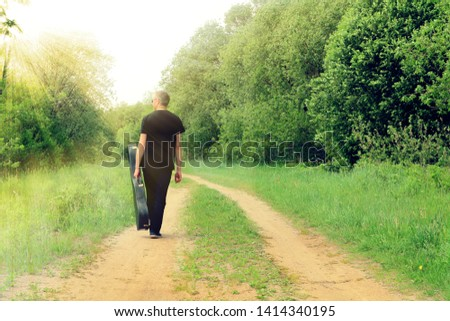 A man in black with a guitar in a case goes into the distance along a path in nature. Musician-guitarist in the sun.