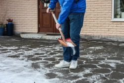 A man in blue jacket, jeans and white sneakers is using a shovel to sprinkle road salt on the paving slabs in front of a house to remove the ice and prevent a slipping accident.