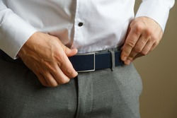 A man in blue pants and a white shirt buttoned a brown leather trouser belt. He has a watch on his hand.