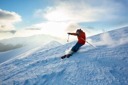 A man in bright sportswear is skiing in mountain area. Blue sky, winter day, sunset, Carpathian mountains.