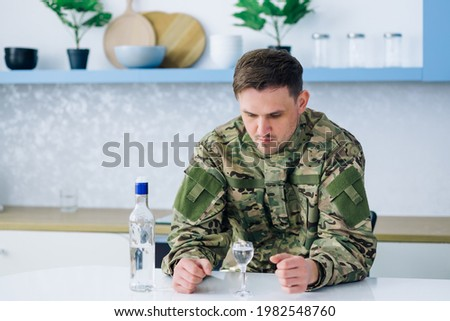 A man in camouflage, drinking alcohol. Depression after hostilities. A sad return home. Return from the army. Post-traumatic disorder. Painful memories. Foto stock ©